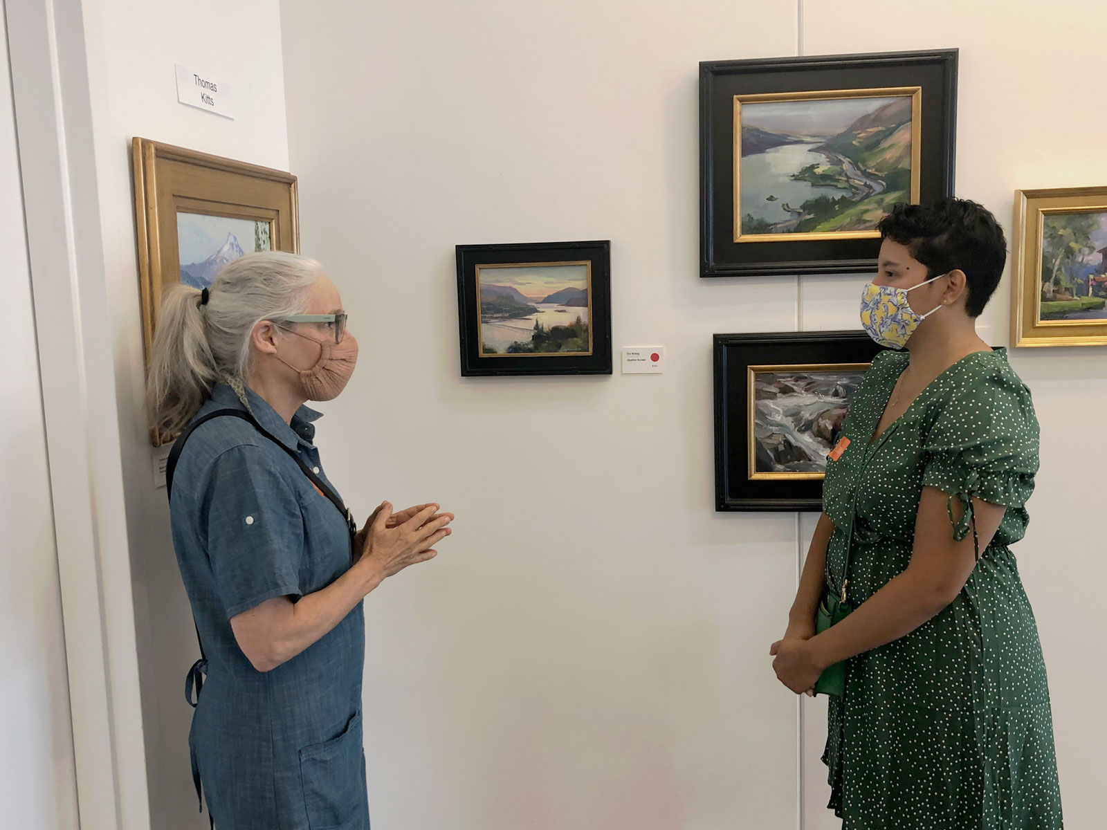 Friends Board Member Lisa Platt (left) and Outdoor Programs Specialist Melissa Gonzalez (right) discuss Elo's winning painting (center)